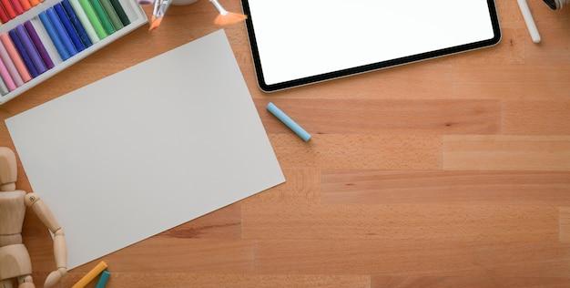 Vista superior do local de trabalho de design moderno com papel de desenho e tablet na mesa de madeira