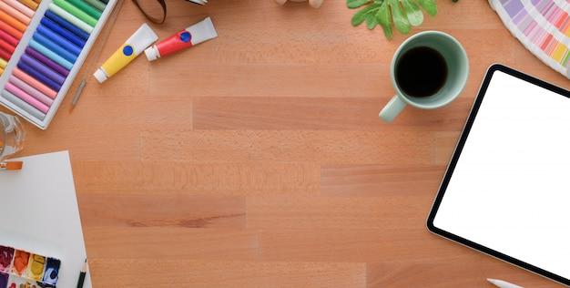 Vista superior do local de trabalho do artista confortável com ferramentas de tablet e pintura na mesa de madeira