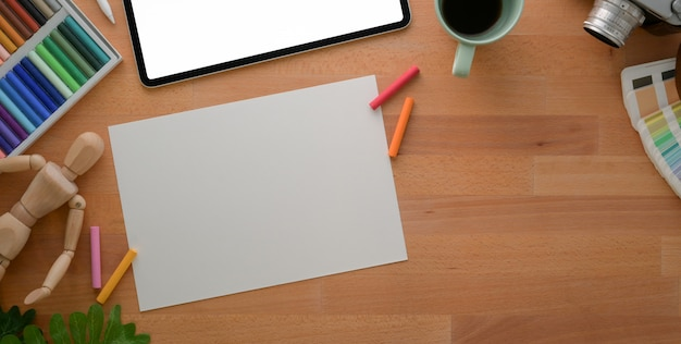 Vista superior do local de trabalho do artista profissional com papel de desenho e ferramentas de pintura