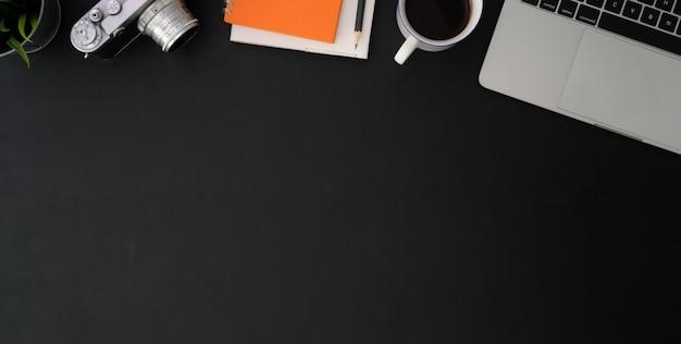 Vista superior do local de trabalho do fotógrafo com câmera, material de escritório e espaço de cópia na tabela preta