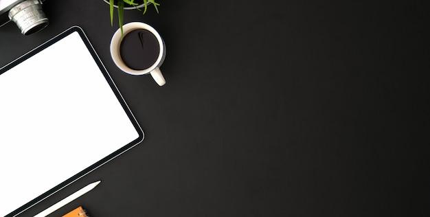 Vista superior do local de trabalho do fotógrafo moderno com tablet de tela em branco e material de escritório na mesa preta