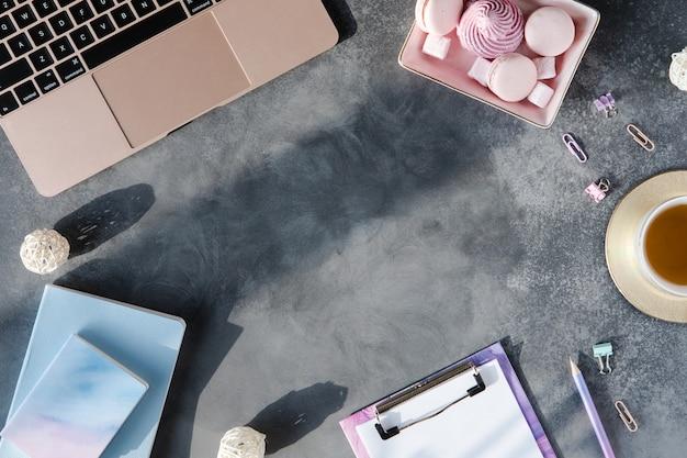 Vista superior do local de trabalho elegante em plano de fundo texturizado cinza com luz do sol e sombras