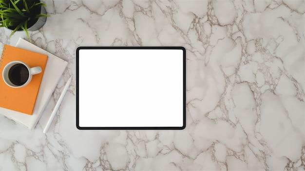 Vista superior do local de trabalho moderno com tablet de tela em branco e material de escritório na mesa de mármore