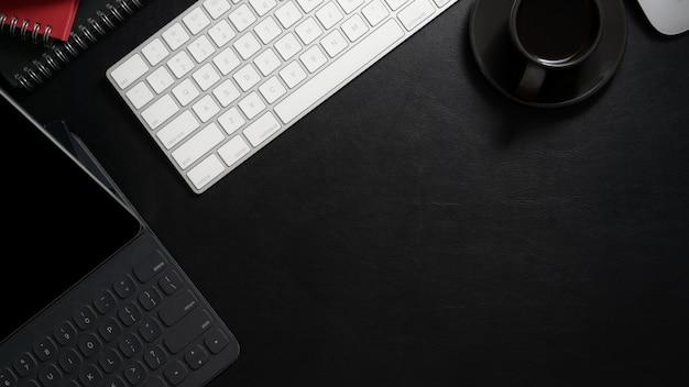 Vista superior do local de trabalho moderno escuro com tablet digital, teclado de computador, xícara de café