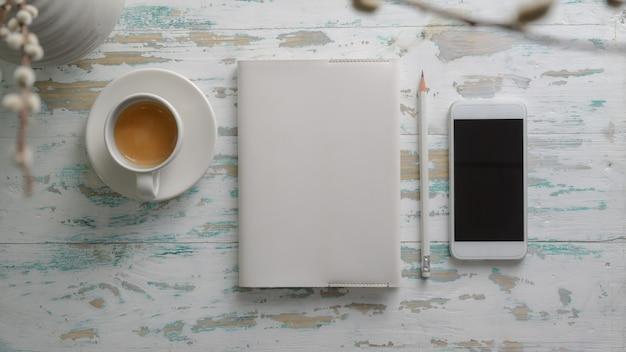 Vista superior do local de trabalho rústico com smartphone, artigos de papelaria e xícara de café