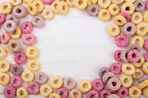 Vista superior do loop colorido e cereais saudáveis em branco com espaço de cópia