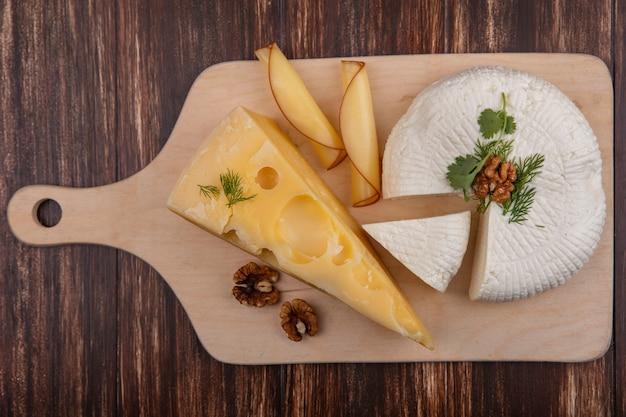 Vista superior do maasdam e queijo feta com nozes em um suporte sobre um fundo de madeira
