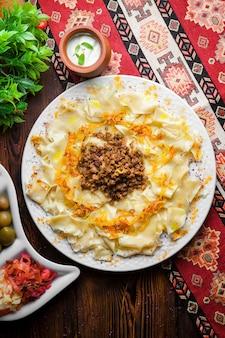Vista superior do macarrão caucasiano guru khingal do azerbaijão com carne picada frita e cebola com molho de creme de leite e picles em uma toalha de mesa vertical