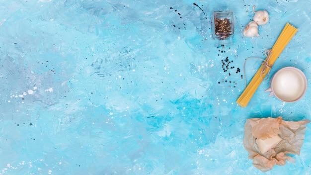 Vista superior do macarrão espaguete cru e ingrediente em pano de fundo azul