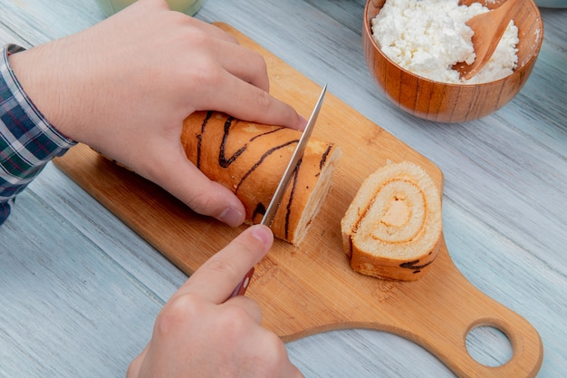 Vista superior do macho mãos corte rolo com faca na tábua com queijo cottage na placa de madeira