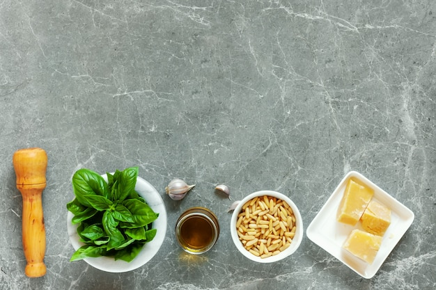 Vista superior do manjericão, pinhões, alho, parmesão e azeite de oliva Foto Premium