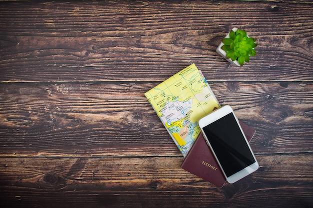 Vista superior do mapa, passaportes e smartphone em uma mesa de madeira para viajar