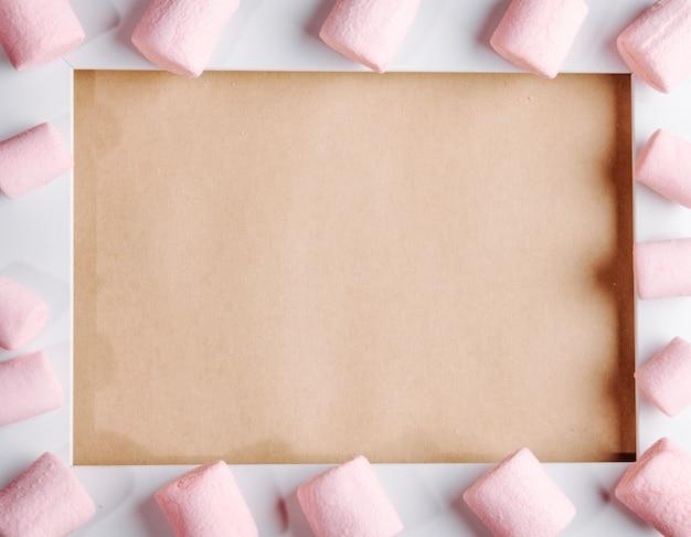 Vista superior do marshmallow colorido disposto em uma moldura vazia