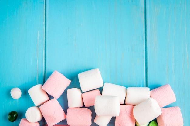 Vista superior do marshmallow na parte inferior, sobre fundo azul de madeira, com espaço de cópia