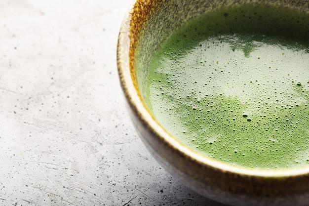 Vista superior do matcha do chá verde em uma bacia na superfície concreta. feche acima do tiro