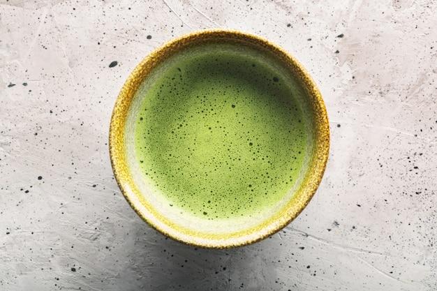 Vista superior do matcha do chá verde em uma bacia na superfície concreta. único objeto