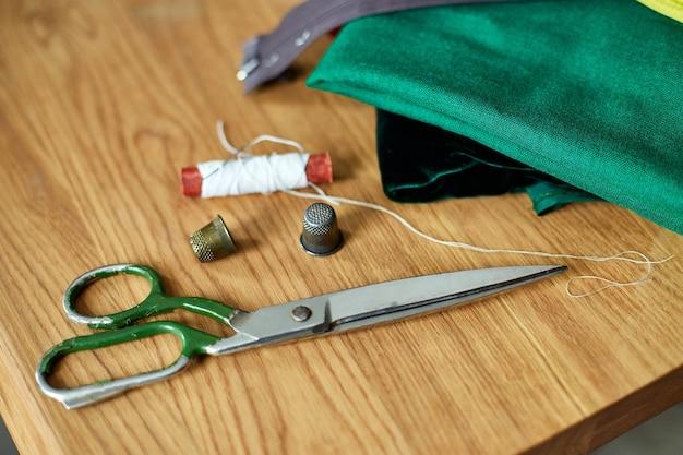 Vista superior do material de costura em uma mesa de madeira: linha de costura, tesoura, pedaços de pano, agulhas, centímetros, padrão.