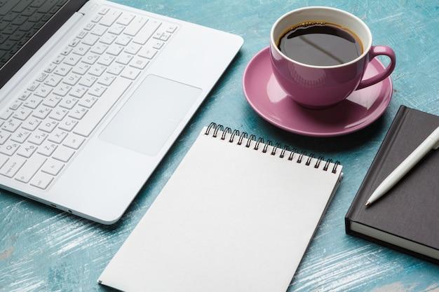 Vista superior do material de escritório com laptop e café