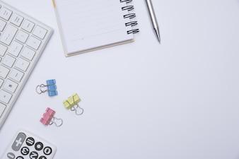 Vista superior do material de escritório e notebook no fundo branco