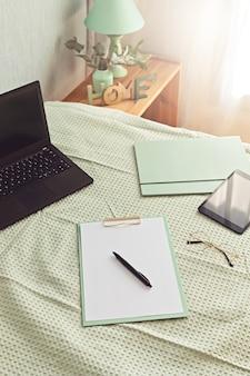 Vista superior do material de escritório na cama, ambiente de trabalho informal com laptop, bloco de notas, xícara de chá. trabalho remoto, home office, freelancer, conceito de auto-isolamento