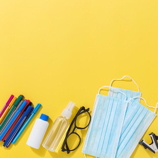 Vista superior do material escolar com lápis e desinfetante para as mãos