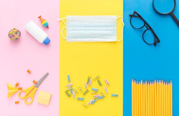 Vista superior do material escolar com máscara médica e lápis