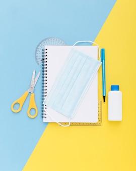 Vista superior do material escolar com notebook e máscara facial