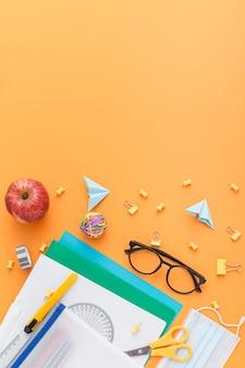 Vista superior do material escolar com óculos e cópia espaço