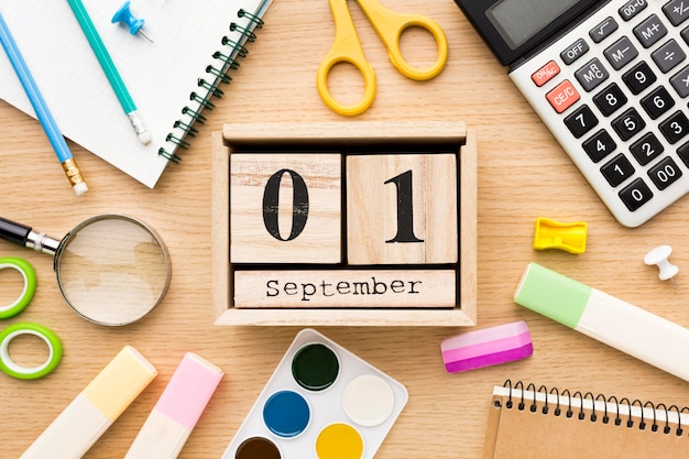 Vista superior do material escolar de volta com calendário e calculadora