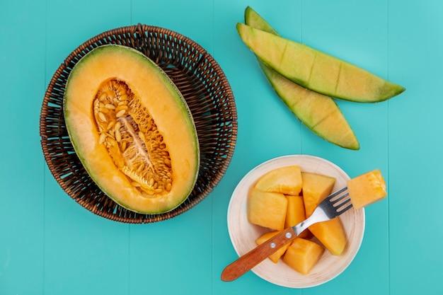 Vista superior do melão doce de melão maduro em uma placa de cozinha de madeira com fatias em uma tigela com garfo na superfície azul