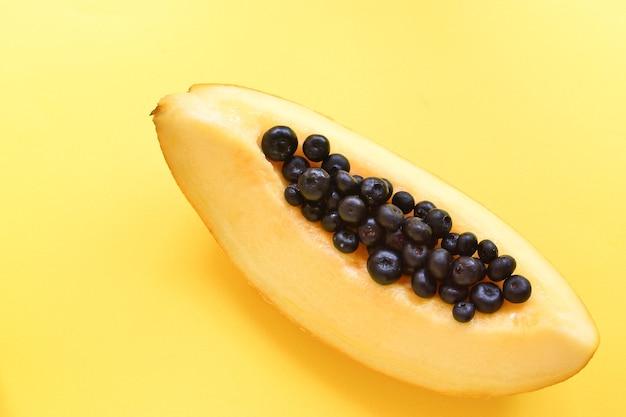 Vista superior do melão maduro fresco sobre fundo amarelo. melão e mirtilo. conceito de comida mínima. alimentos criativos.