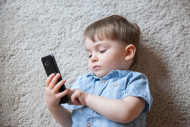 Vista superior do menino brincando com um telefone em vez de brinquedos de bebê real.