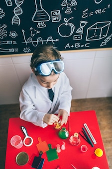 Vista superior do menino cientista brincando com líquidos químicos sobre a mesa e o quadro-negro com desenhos