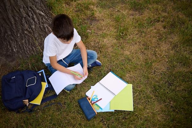 Vista superior do menino da escola focada em escrever em folhas em branco vazias de uma pasta de trabalho, fazendo lição de casa sentado na grama verde do parque, depois da escola. acessórios escolares e mochila deitada na grama