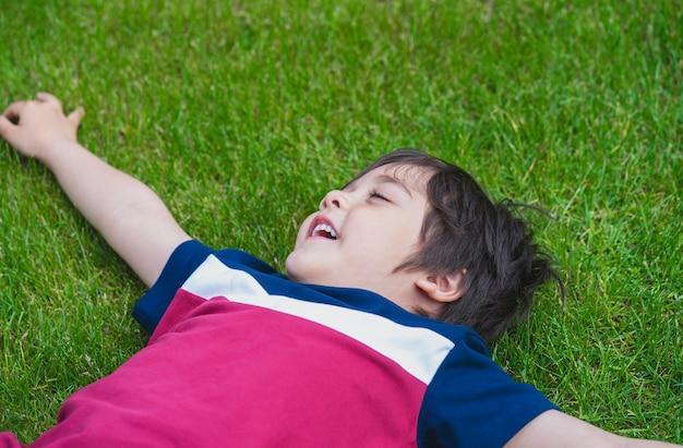 Vista superior do menino deitado no gramado do parque,