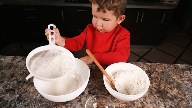 Vista superior do menino peneirando farinha em uma peneira