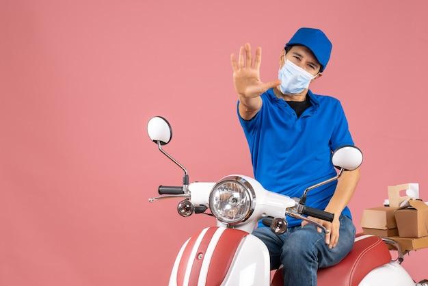 Vista superior do mensageiro com máscara médica usando chapéu, sentado na scooter e mostrando cinco em fundo de pêssego pastel