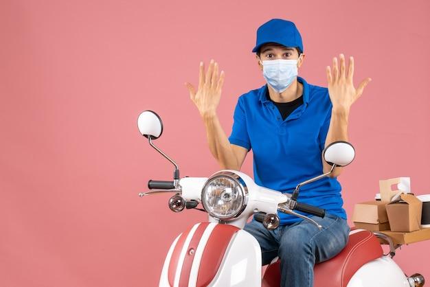 Vista superior do mensageiro com máscara médica usando chapéu, sentado na scooter e sentindo curiosidade sobre o fundo cor de pêssego