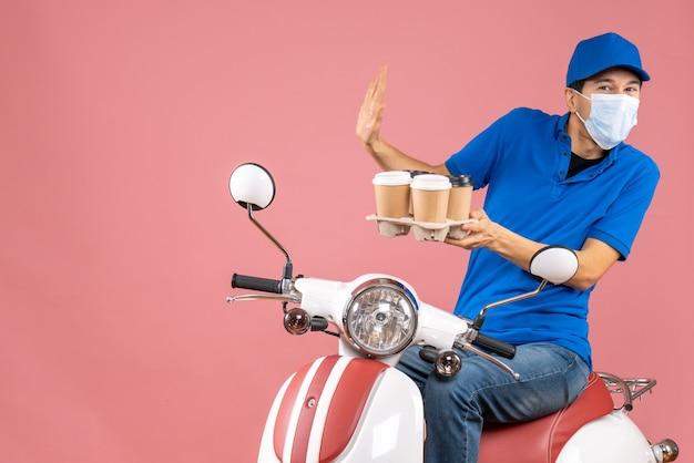Vista superior do mensageiro com medo e máscara, usando um chapéu, sentado na scooter, mostrando pedidos em fundo de pêssego pastel