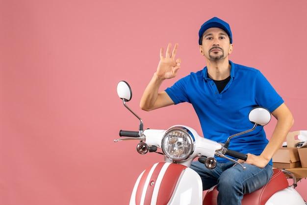 Vista superior do mensageiro confiante usando um chapéu, sentado na scooter, entregando pedidos e fazendo gestos de óculos em um fundo cor de pêssego