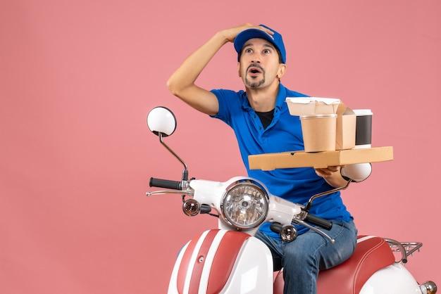 Vista superior do mensageiro surpreso com chapéu, sentado na scooter, olhando para cima em pêssego