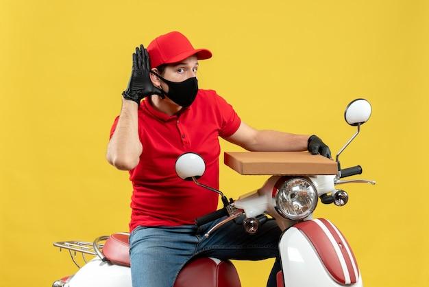 Vista superior do mensageiro usando blusa vermelha e luvas de chapéu na máscara médica, sentado na scooter, mostrando a ordem de ouvir as últimas fofocas