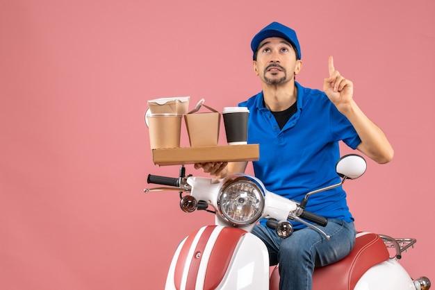 Vista superior do mensageiro usando chapéu sentado na scooter apontando para cima no fundo cor de pêssego