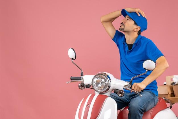 Vista superior do mensageiro usando um chapéu sentado na scooter, entregando pedidos pensando profundamente em um fundo de pêssego pastel