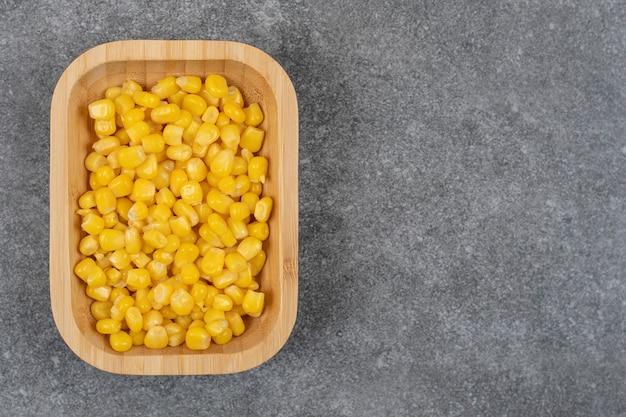 Vista superior do milho doce enlatado em uma tigela de madeira.