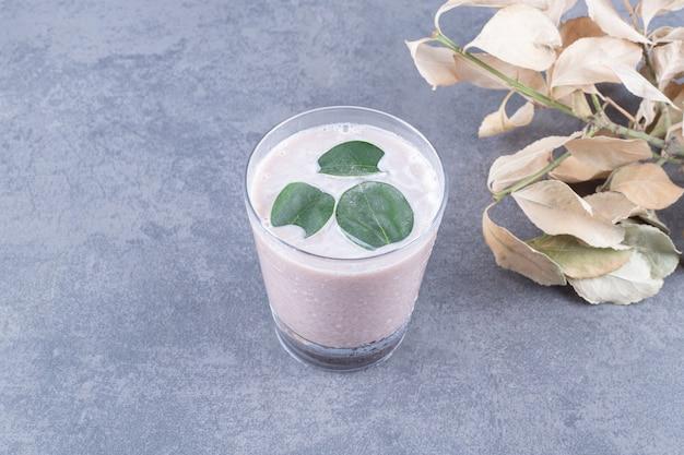 Vista superior do milk-shake cremoso com hortelã em fundo cinza.
