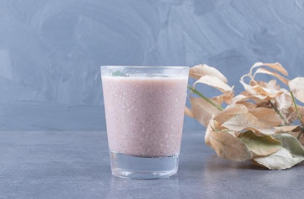 Vista superior do milk shake cremoso em fundo cinza.