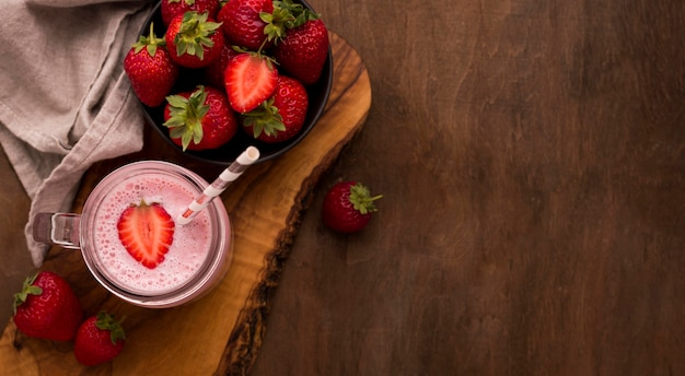 Vista superior do milkshake de morango com canudo e copie o espaço