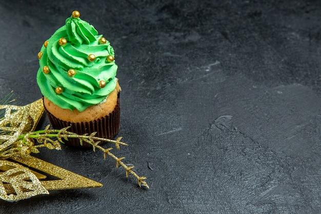 Vista superior do mini cupcake da árvore de natal e enfeite dourado pendurado na superfície escura