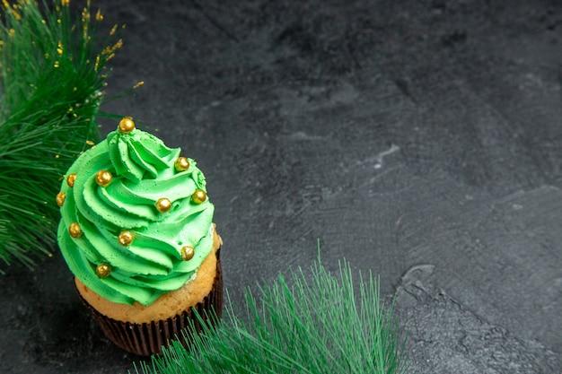 Vista superior do mini cupcake da árvore de natal e galhos de árvore de natal na superfície escura